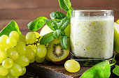 1 glass of  yogurt with fresh kiwi, green Apple,  grapes,  spinach and mint on a wooden background close up