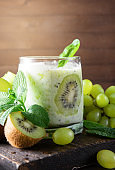 1 glass of  yogurt with kiwi  and mint , fresh  green  grapes on a wooden background