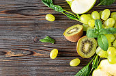 fresh green halves kiwi, grapes, ,  spinach,  mint top view , on a wooden background