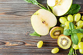 fresh green kiwi, grapes, Apple halves,  mint top view , on a wooden background,