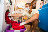 Young Adult Man Wearing Protective Face Mask and Gloves While Inserting Dirty Laundry into Washing Machine at Home