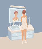 Young woman wearing pajama putting night cream on her skin