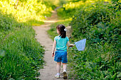 beautiful baby girl in a blue T-shirt and shorts walks along the path with a butterfly net. greenery around