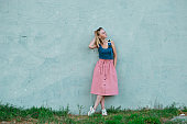 blonde girl in blue top and light pink skirt in sports shoes on the background of blue wall. horizontal photography
