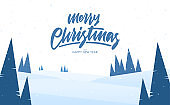 Blue winter snowy landscape with hand lettering of Merry Christmas and Happy New Year.