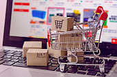 Parcel or Paper cartons in shopping cart on a laptop keyboard.