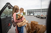Single mother carrying groceries and her baby after shopping