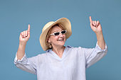 Woman in summer hat and sunglasses pointing up having great mood smiling
