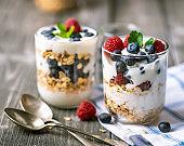 White yogurt in glass jar with fruits on grey background.