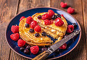 Sliced sweet homemade pancakes with raspberries and blueberries on blue plate on dark wooden desk.