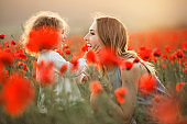 Beautiful smiling child girl with young mother are having fun in field of poppy flowers over sunset lights