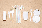 Disposable single use plastic objects cause pollution of the environment, top view on sand