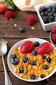Breakfast of corn flakes with blueberries and strawberries in white bowl on wooden table.