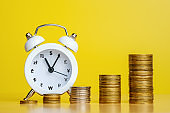 Stacks of coins in row ascending and alarm clock with currency signs
