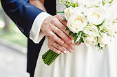 Cropped close up photo, of chic virile luxurious trendy The and a wedding bouquet. bride and groom holding on hands standing on wedding ceremony . Close-up. Wedding accessories.