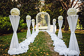 The arc for the wedding ceremony is decorated with flowers and columns in the open air. Wedding decor. Photo Zone.