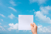Woman hand holding white paper with blue sky and cloud background.