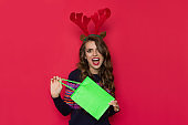 Happy Young Woman In Christmas Reindeer Showing Green Shopping Bag And Shouting