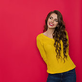 Smiling Young Woman In Yellow Sweater Looks Aside