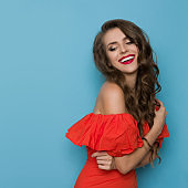 Happy Beautiful Woman In Elegant Red Dress Looking Over The Shoulder And Smiling