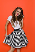 Young Beautiful Woman Is Posing In Striped Skirt