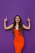 Happy Young Woman In Tight Orange Dress Is Pointing Above Head And Looking Up
