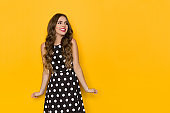 Happy Young Woman In Black Cocktail Dress In White Polka Dots