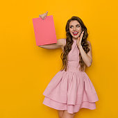 Happy Beautiful Young Woman In Pink Cocktail Dress Is Holding Pink Sheet Of Paper And Talking