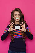 Smiling Woman In Sweater With Colorful Pattern Holds White Card In Front Of Her
