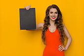 Beautiful Young Woman Is Showing Black Sheet Of Paper And Smiling