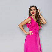 Elegant Young Woman In Pink Dress Is Looking Away And Smiling