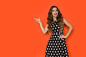 Beautiful Young Woman Is Black Coctail Dress In Polka Dots Is Pointing At Orange Copy Space And Smiling