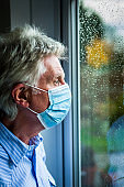 Depressed senior man wearing face mask looking out of rainy window