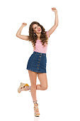 Happy Woman In Jeans Mini Skirt And Wedge Shoes Is Standing On One Leg With Arms Raised And Cheering
