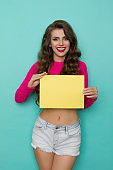 Young Smiling Woman Holds Yellow Empty Card