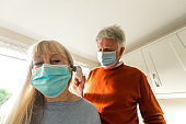 Senior couple wearing face masks and measuring temperature at home during Covid-19 pandemic