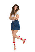Cheerful Young Woman In Jeans Mini Skirt And Red High Heels Is Standing On One Leg