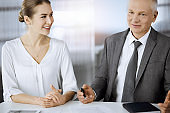 Elderly businessman and woman sitting and communicating in sunny office. Adult business people or lawyers working together as a partners and colleagues at meeting