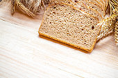 Home baked bread. Rye bakery with crusty loaves and crumbs. Fresh rustic traditional bread with wheat grain ear or spike plant on natural wooden background. Design element for bakery product label.