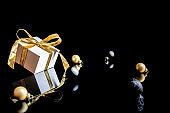 Happy winter holiday. White gift with golden bow, gold balls and new year tree in xmas decoration on dark background for greeting card. Decoration and copy space for your text.