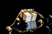 Happy 2021. White gift box with golden ribbon, New Year balls and winter tree in Christmas composition on black background for greeting card. Decoration and copy space for your text.