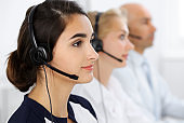 Call center operators at work. Focus at beautiful latin american woman in headset