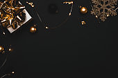 Christmas gift. White gift with golden bow, gold balls and sparkling lights garland in xmas decoration on dark background for greeting card. Xmas backdrop with space for text.