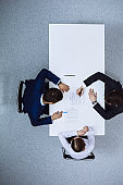 Group of business people and lawyer discussing contract papers sitting at the table, view from above. Businessman is signing document after agreement done