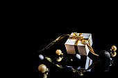 Gift ribbon gold. White gift box with golden ribbon, New Year balls and winter tree in Christmas composition on black background for greeting card. Winter festive composition with copy space.