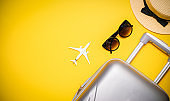Sea background. Travel accessories with suitcase, white plane, palm leaves in minimal trip vacation concept on yellow background. Summer vacation and product advertisement concept.