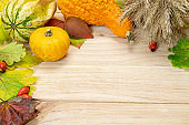 Autumn pattern. Natural harvest with rye spike orange pumpkin, fall dried leaves, red berries and acorns, chestnuts on wooden background. Beauty bright autumnal nature background. Harvest.