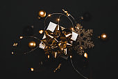 Winter design. White gift box with golden ribbon, New Year balls and sparkling lights garland in Christmas composition on black background for greeting card. Xmas backdrop with space for text.