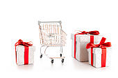 Products cart. Trolley cart for supermarket with christmas or birthday gift box isolated on white background. Minimalism style. Creative design for valentine, xmas surprise package.