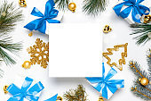 Surprise box. White gifts with blue bow, golden balls and Christmas tree in xmas decoration on white background for greeting card. Flat lay, top view, copy space.